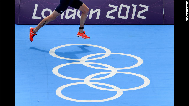 Britain's Alistair Brownlee runs over Olympic rings on his way to a win in the men's triathlon.