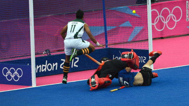 Facundo Callioni of Argentina, right, scores a goal against South Africa during the field hockey preliminary round match.