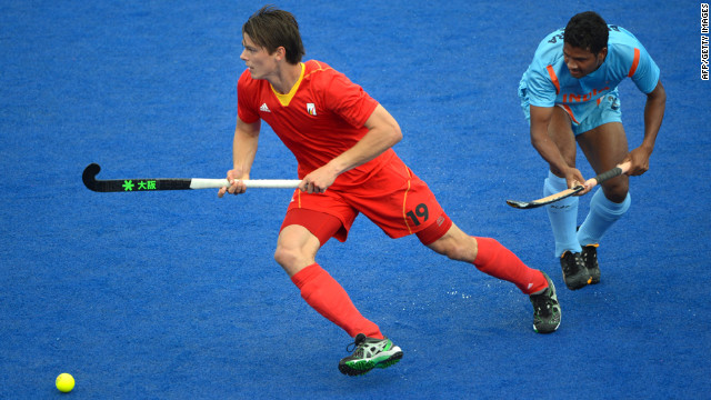 Felix Denayer, left, of Belgium dribbles past Birendra Lakra of India during the field hockey preliminary round match between India and Belgium.