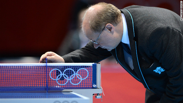 An Olympic official comforts the table-tennis table after it absorbs another butt-kicking.