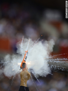 A referee fires the gun to start a race of the the London 2012 Olympic Games cycling event at the velodrome in the Olympic Park.