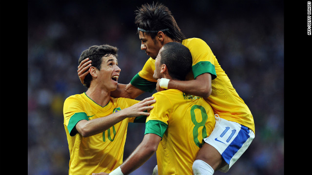 Brazil midfielder Oscar, left, and Brazil forward Neymar, right, congratulate goal scorer Brazil defender Romulo, second right, during the London 2012 Olympic men's football semifinal match between Brazil and South Korea.