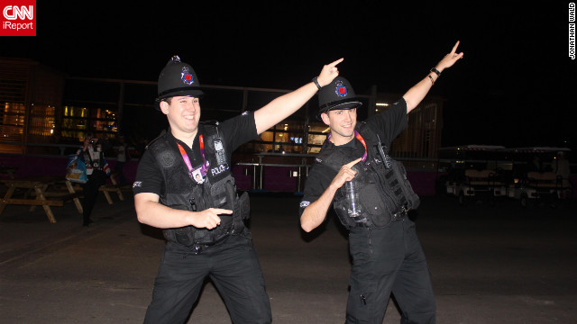 Two policemen at the Olympic Park celebrate Usain Bolt's victory in the 100 metres with his signature 'Bolt arms' salute. 