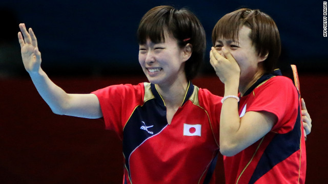 Japanese table tennis players Kasumi Ishikawa, left, and Sayaka Hirano weep after beating Singapore in the women's team semifinal match.