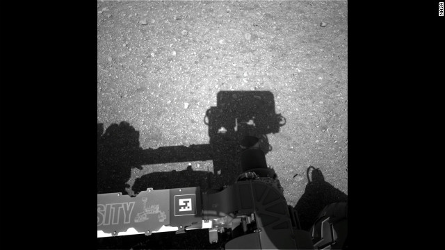 "This first image taken by the Navigation cameras on Curiosity shows the shadow of the rover's now-upright mast in the center, and the arm's shadow at left. The arm itself can be seen in the foreground. The ""augmented reality"" or AR tag seen in the foreground can be used in the future with smart phones to obtain more information about the mission."