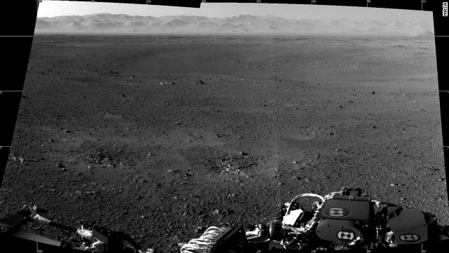 "This is a composite image made from two full-resolution images of the Martian surface from the Navigation cameras on the rover, which are located on its ""head"" or mast. The rim of Gale Crater can be seen in the distance beyond the pebbly ground. The foreground shows two distinct zones of excavation likely carved out by blasts from the rover's descent stage thrusters."