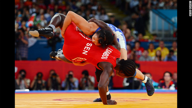 Senegal's Isabelle Sambou, in red, and Canadian Carol Huynh compete in women's freestyle 48-kilogram wrestling on Day 12 of the London 2012 Olympic Games.
