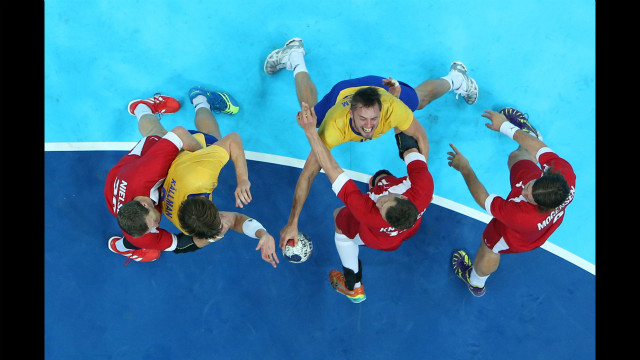 Sweden's Jonas Larholm fights through Danish handball players during the men's quarterfinal match. Sweden beat Denmark 24-22.