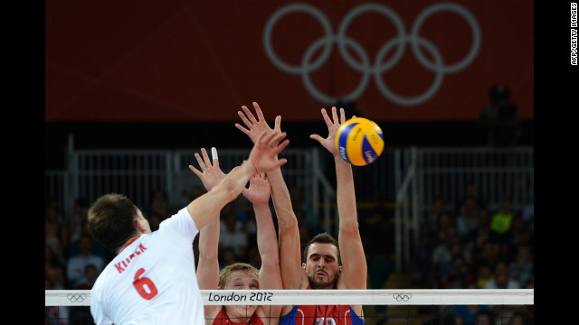 Poland's Bartosz Kurek, left, spikes as Russia's Sergey Grankin, center, and Alexander Volkov attempt to block during the men's quarterfinal volleyball match.