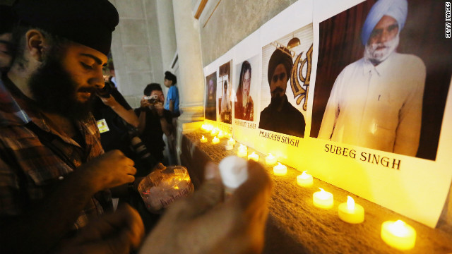 Photos of the victims are displayed during a candlelight vigil Wednesday in New York's Union Square. Six people were killed in the shooting Sunday, August 5, near Milwaukee.