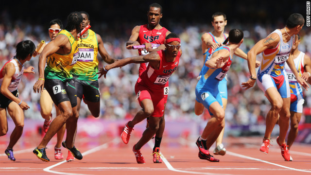 U.S. runner Joshua Mance passes the baton to teammate Tony McQuay during the men's 4 by 400-meter relay round 1 heats.