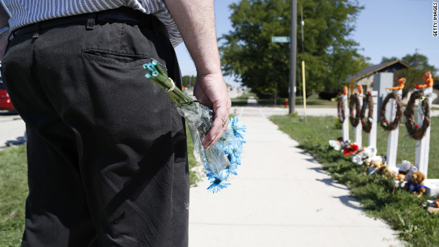 A man visits the makeshift memorial near the Sikh Temple of Wisconsin on Tuesday.