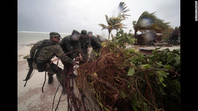 Soldiers remove fallen branches and other debris from a beach in Mahahual.
