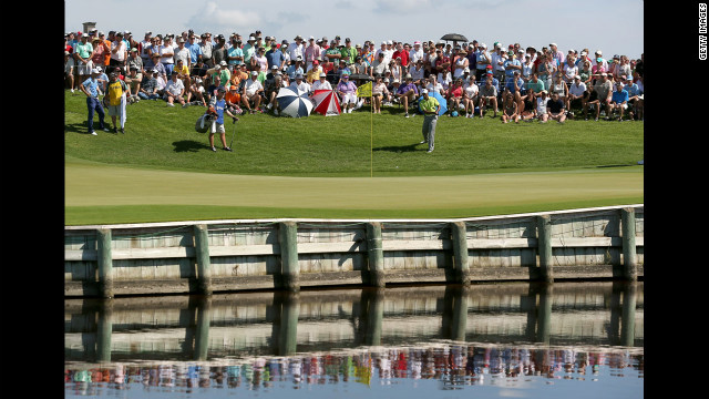 Woods hits a shot onto the 17th green during round one.
