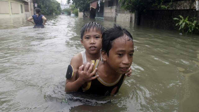 Children slog through floodwaters in Pasig City, east of Manila.