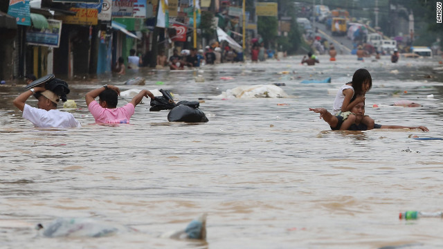 Residents move through chest-high floodwaters in Marikina City, east of Manila.