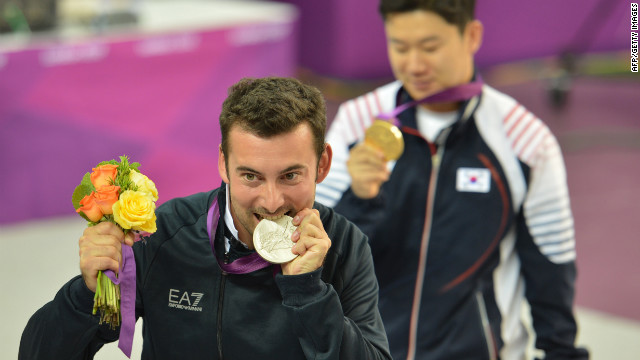 Italy's Luca Tesconi bites his silver medal as gold medalist South Korea's Jin Jong-oh stands behind him. They competed in the 10-meter air rifle men's final. 