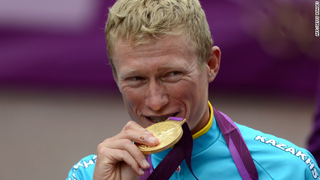 Alexander Vinokourov of Kazakhstan bites his gold medal after winning the men's road race cycling event.