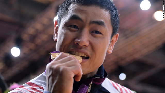 South Korea's Song Dae-nam bites his gold medal after winning a judo event.