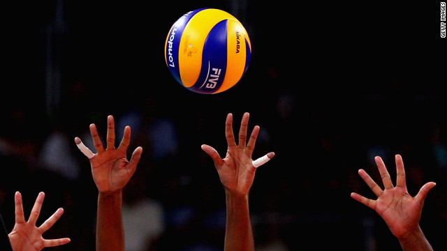 No. 16 Fernanda Rodrigues and No. 6 Thaisa Menezes of Brazil defend the ball from No. 18 Saori Kimura of Japan during the women's volleyball semifinal match.