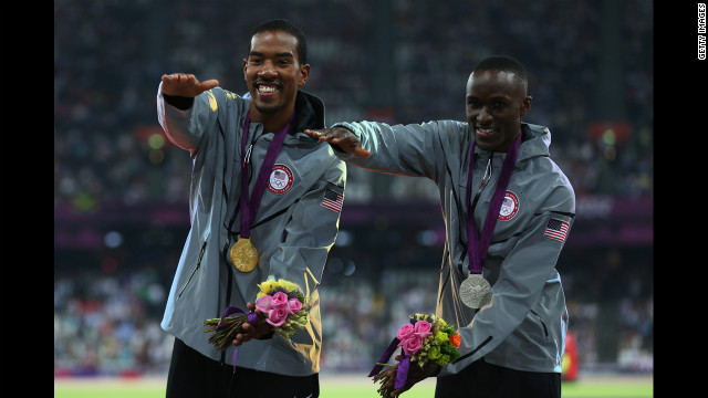 "Gold medalist Christian Taylor and silver medalist Will Claye, also of the United States, celebrate during the medal ceremony for the men's triple jump. Both athletes attended the University of Florida and are seen doing the ""Gator chomp."""