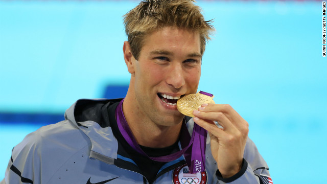 Matt Grevers of the U.S. celebrates with his gold medal during the medal ceremony for the men's 100-meter backstroke.