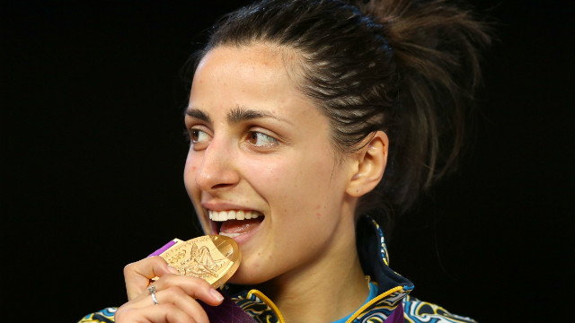 Yana Shemyakina of Ukraine bites her gold medal after defeating Britta Heidemann of Germany in the women's epee individual fencing finals.