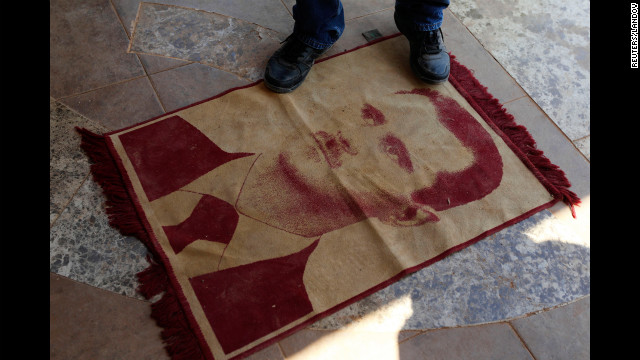 A man steps on a carpeted image of Syrian President Bashar al-Assad in Anadan, northwest of Aleppo, on Wednesday, August 8. The fighting has taken a toll on al-Assad's regime, which has been hit by assassinations and political and military defections.
