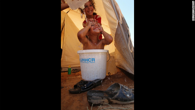 Syrian refugees bathe Wednesday at Al Zaatri U.N. camp in<br /> 1000<br /> the Mafraq, Jordan, near the border with Syria. The recent shelling has led thousands of residents to flee Syria.