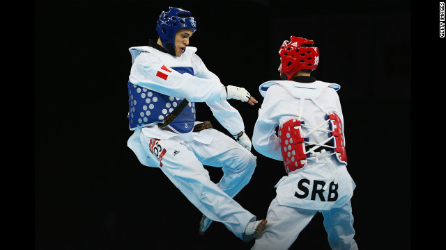 Peru's Peter Lopez Santos, left, faces off against Damir Fejzic of Serbia in the preliminary round men's under 68-kilogram taekwondo match.