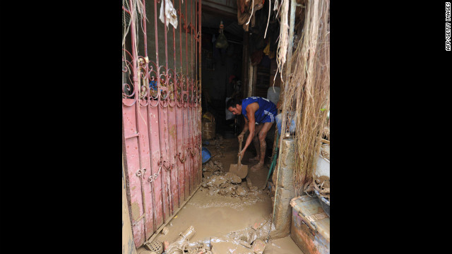 A resident shovels mud from his house Friday in the village of Tumana.