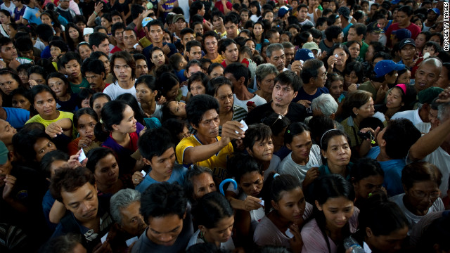 Thousands line up for food relief Friday in Paombong outside Manila.