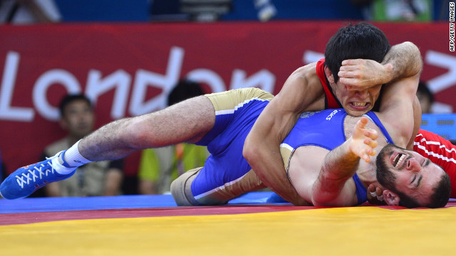 Kazakhstan's Daulet Niyazbekov, in red, wrestles Russia's Dzhamal Otarsultanov during the men's 55-kilogram freestyle semifinal match.