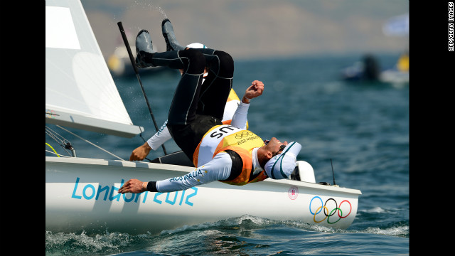Australia's Malcolm Page leaps off the boat as teammate Mathew Belcher sails on after winning the gold in the men's 470 sailing class.