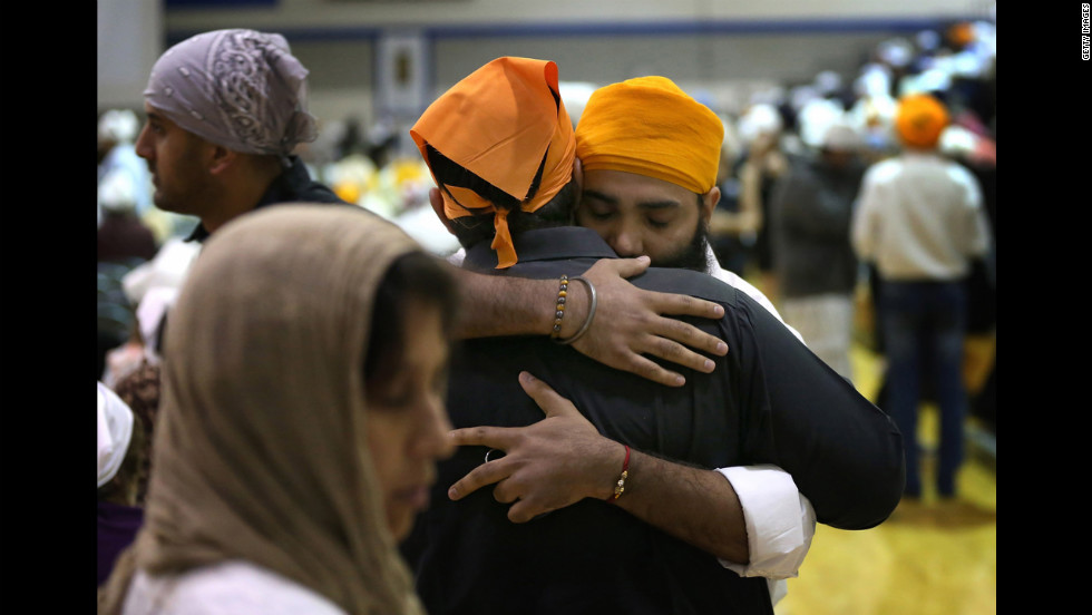 Mourners embrace at a memorial service Friday, August 10, for the six people killed in last weekend's shooting at a Sikh temple in Oak Creek, Wisconsin. Family and friends gathered at Oak Creek High School in suburban Milwaukee.