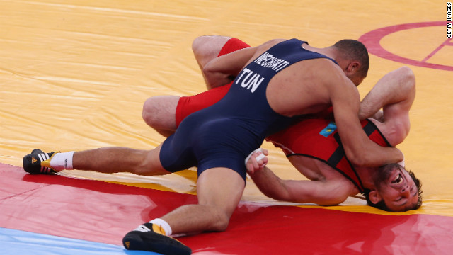 Kazakhstan's Abdulkhakim Shapiyev, right, fights Bilel Ouechtati of Tunisia during the men's freestyle wrestling (74-kilogram) 1/8 final bout.