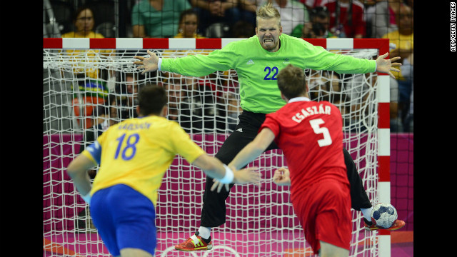 Hungary's center back Gabor Csaszar, right, shoots against Sweden's goalkeeper Johan Sjostrand during the men's semifinal handball match against Sweden.