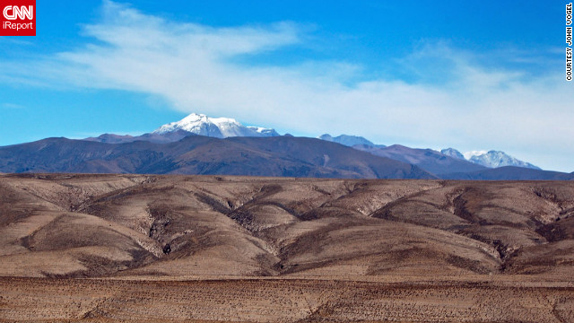"<a href='http://ireport.cnn.com/docs/DOC-825313 '>John Vogel</a> was on a minibus traveling between the city of Arequipa and Colca Canyon in Peru when he saw this odd landscape. ""Looking at the photo now, it almost looks like two photos combined into one photo. That's how great I find the contrast between the dark rocky foreground and the bright blue sky with the snow-capped volcano."""