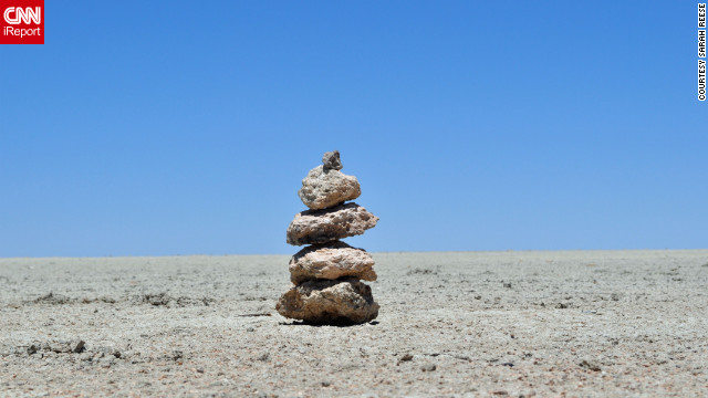 "Sarah Reese snapped this shot of a stack of rocks while lying down in the salty dirt of the Etosha Pan, a flat saline desert in the middle of Namibia's Etosha National Park. ""There are no other rocks near this small stack. It was really odd to see them in this otherwise empty space,"" she says. The rocks are a cairn, or a stack of stones used as a marker."
