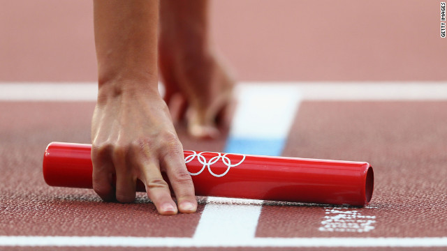 An athlete holds the baton during the women's 4 x 400-meter relay round 1 heats.