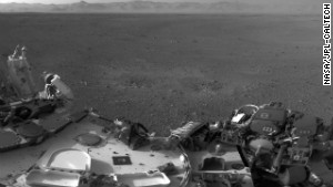 Two blast marks from the descent stage\'s rockets can be seen in the center of this images. Also seen is Curiosity\'s left side. This image is a mosiac of images taken by the rover\'s naviagtion camers.
