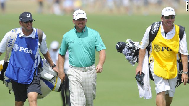 Graeme McDowell walks with caddies.