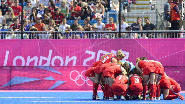 Britain's field hockey team tends to a wounded bird before their match.