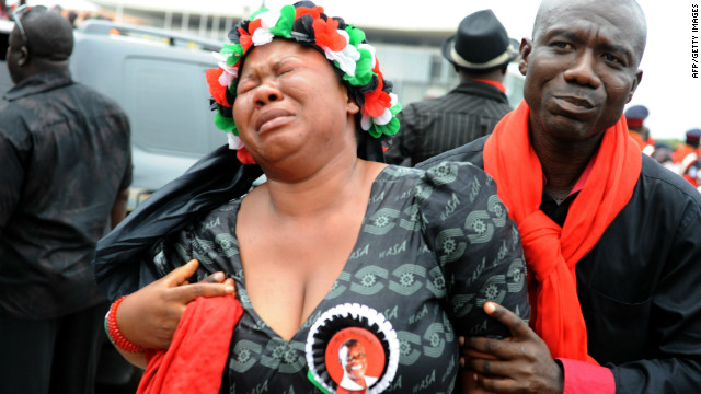 Ghana began three days of funeral rites for its late president on Wedneday. A man holds a supporter of the ruling National Democratic Congress in tears after viewing the body of Mills.