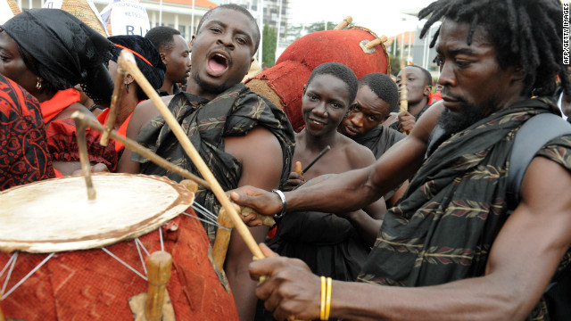 A mourner plays his drum amid a long q<br />