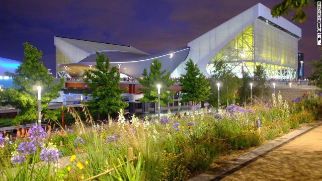The Aquatic Centre shone neon yellow beyond wildflower planting on the banks of the River Lea. The venue's curved center, designed by architect Zaha Hadid, will remain after the Games. The sweeping wings either side are temporary stands that will be dismantled at the end of the Games.