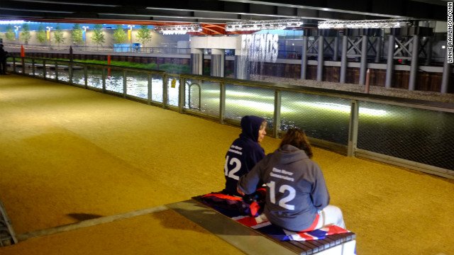 Two Eton Manor volunteers took a moment for a quiet conversation in front of the &quot;bit.fall&quot; installation by artist Julius Popp. Words taken from live news headlines are projected at random onto five man-made waterfalls under the Stratford Gate bridge.