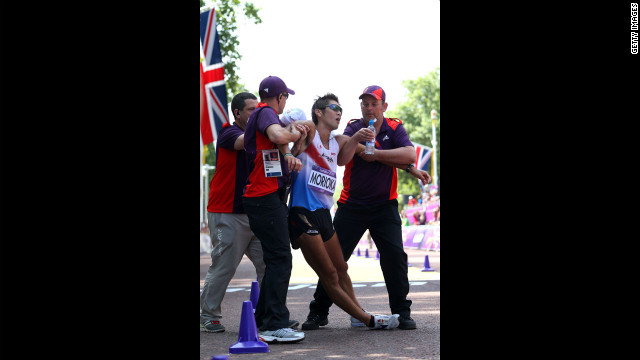 Japan's Koichiro Morioka gets assistance as he crosses the finish line during the men's 50-kilometer walk.
