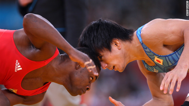 Japan's Kenichi Yumoto, right, wrestles Cuba's Yowlys Bonne Rodriguez in the men's freestyle final match.