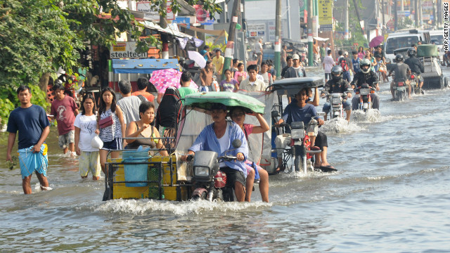 Residents commute Saturday along a flooded stretch of road in Calumpit.